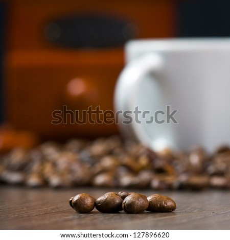 Coffee antique grinder, coffee beans and cup of coffee.