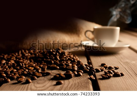 Coffee background with beans and white cup. Dark atmosphere and copy space.
