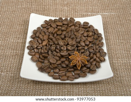 coffee bean are spilled on a saucer with a anise on a background sacking