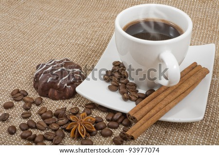 coffee bean, cinnamon, anise, chocolate thin captain and hot coffee on a background sacking