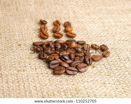 Coffee bean coffecup icon on jute background.