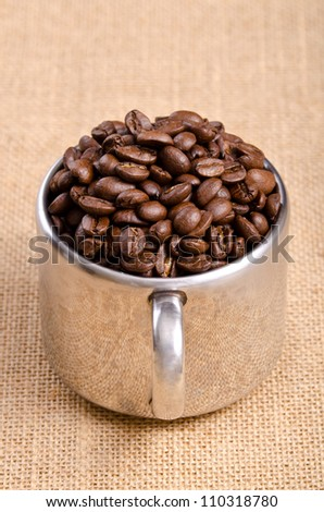 Coffee Bean in Stainless Cup on Natural Sack Background