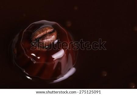 Coffee bean on malted chocolate. Liquid chocolate