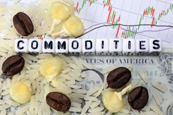 Coffee bean, rice, corn and letter cube on dollar and candle stick chart background. Conceptual image of commodity trading.