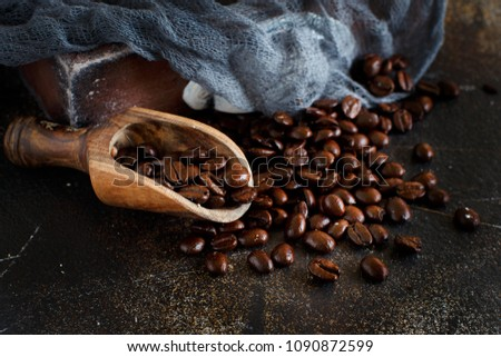 Coffee beans and a wooden spoon  on a dark background close up #1090872599