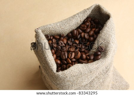 Coffee beans and burlap sack on wood floor.