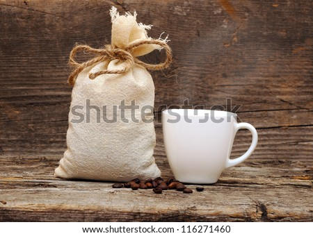 coffee beans and burlap sack on wooden background - stock photo