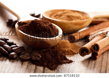 Coffee beans and cinnamon milled closeup in wooden spoons