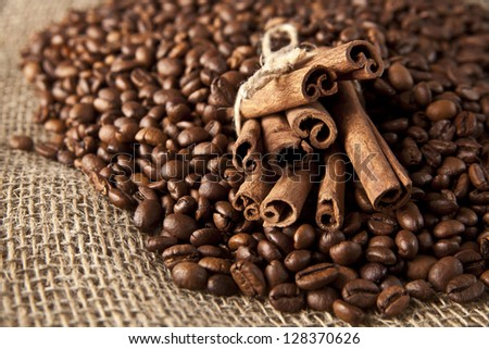Coffee beans and cinnamon on a sacking background