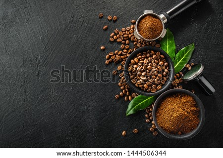 Coffee beans and coffee powder with tamper on dark background. Coffee concept. Coffee background. Flat Lay.