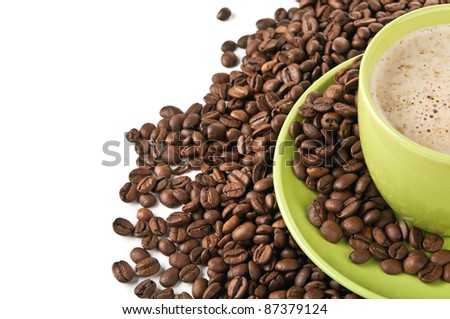 coffee beans and green cup isolated on a white background