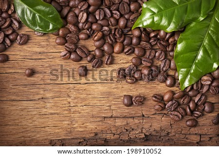 Coffee beans and green leaves on wooden background