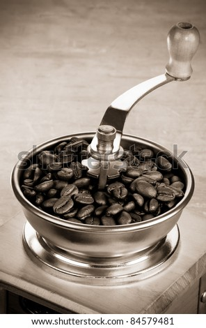 coffee beans and grinder on wood background