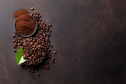 Coffee beans and ground powder on stone background. Top view with copy space for your text