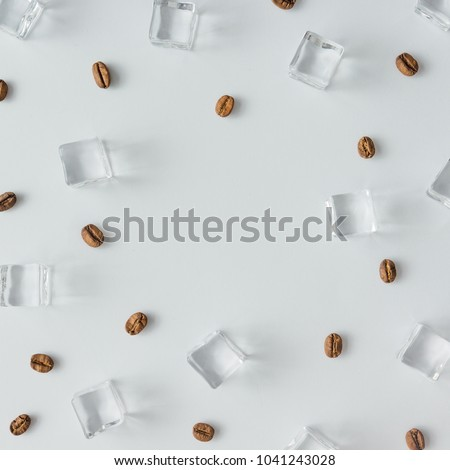 Coffee beans and ice cubes pattern on bright background. Flat lay summer drink minimal concept.