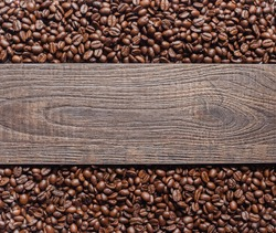 Coffee beans and wooden texture background.