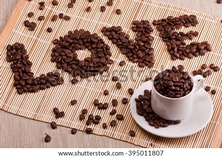 Coffee beans are laid out on a table on a straw or wooden stand. Coffee is laid out in the shape of a LOVE. Good for Valentine's day, at the time of declaration of love, makes an offer