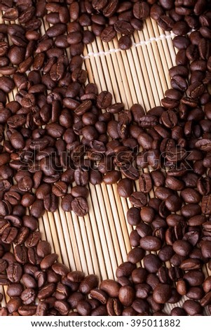 Coffee beans are laid out on a table on a straw or wooden stand. Coffee is laid out in the shape of a heart. Good for Valentine's day, at the time of declaration of love, makes an offer