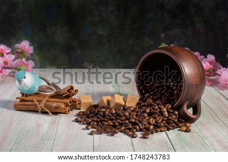 coffee beans are scattered from an upturned earthenware mug ,cinnamon sticks and sugar cubes on a light wooden background
