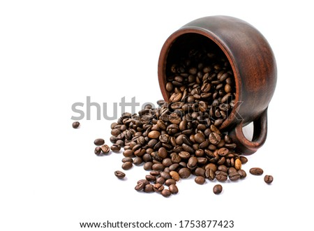 coffee beans are scattered from an upturned earthenware mug on a white isolated background