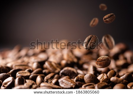 Coffee beans at the fabrique. Coffee beans fall on the table. Background made of falling down fresh coffee beans with copy space Stok fotoğraf ©