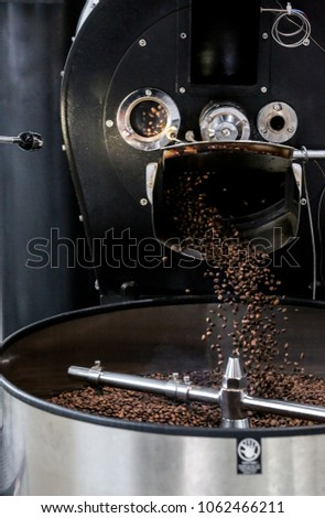 Coffee Beans being processed through machine falling into mixing drum.  #1062466211