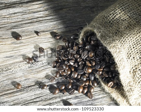 coffee beans fallen out of a jute bag located on weathered wood