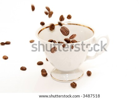 Coffee beans falling on a cup, with focus on the beans in front
