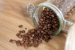 Coffee beans falling out of a glass jar close-up, top down view, rustic style, interior kitchen design, retro, warm tones