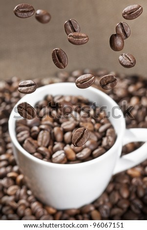 coffee beans floating on a white cup