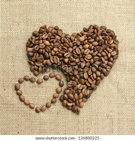 Coffee beans, grain two hearts on background of sacking, bagging. Valentine's Day or Wedding, love, black, frame. Heart shaped Coffee Beans. Big and small heart. Retro
