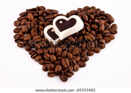 Coffee beans heart with heart-shaped candy on white background