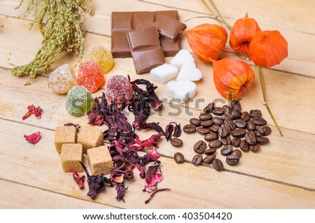 Coffee beans, hibiscus tea, lump sugar, chocolate, marmalade and physalis on wooden background #403504420