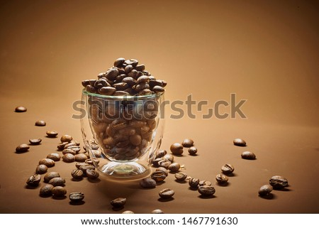 coffee beans in a an espresso cup on a brown background. fresh roasted espresso beans in a glass cafe