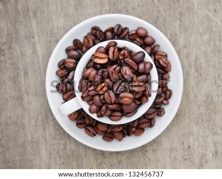 coffee beans in a cup on a wooden background