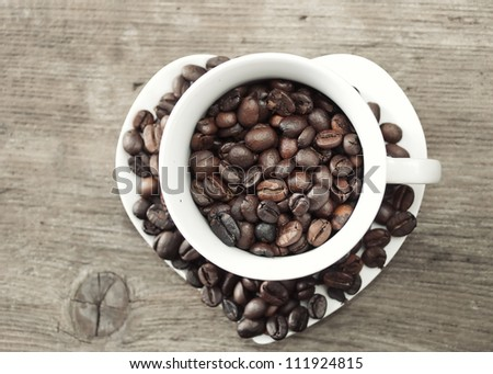 coffee beans in a cup on old wooden plank - stock photo