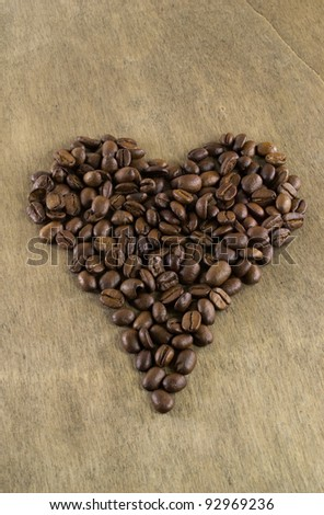 Coffee beans in a heart shape on a wooden table background
