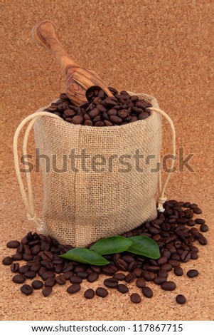 Coffee beans in a hessian drawstring sack and loose with leaf sprigs and olive wood scoop over cork background.
