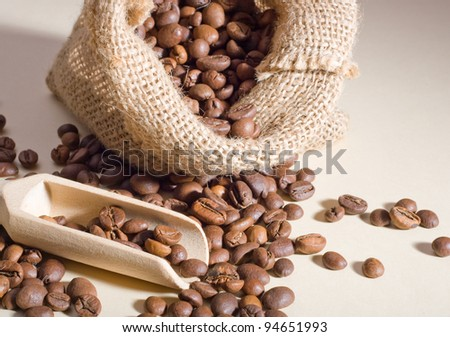 Coffee beans in a linen bag and a wooden spoon.