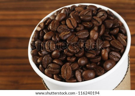 Coffee beans in a paper cup on a  wooden textured surface