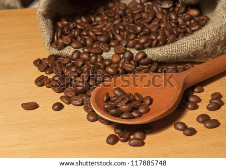 Coffee beans in a sack and a wooden spoon on a wooden background