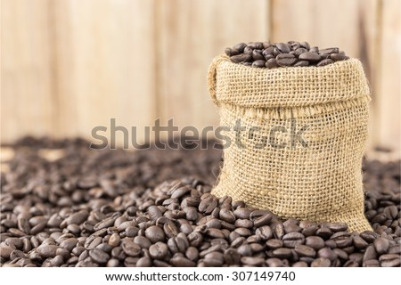 coffee beans in bag on roasted coffee seed and wooden background