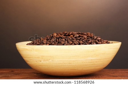 Coffee beans in bamboo bowl on table on brown background