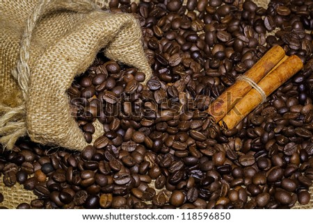 coffee beans in burlap bag with cinnamon sticks