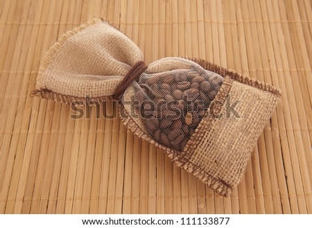 Coffee beans in canvas sack on baboo background