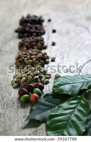 Coffee beans in different roast levels lying on rustic wooden board.