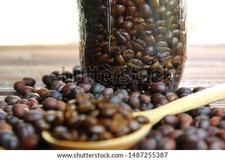 coffee beans in glass bottle .dried coffee beans with roasted coffee beans .coffee beans on wood spoon on brown wood floor .
