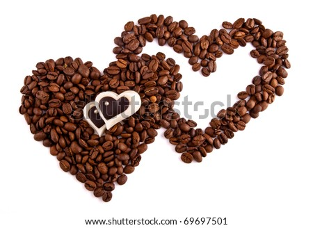Coffee beans in heart shape with heart-shaped candies isolated on white background