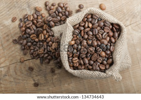 coffee beans in jute bag on wooden table - stock photo