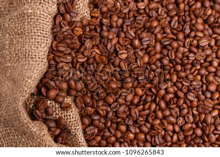 coffee beans in jute bag on wooden table. Burlap sack full of coffee beans on wood table #1096265843